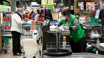 A staff member wipes down the checkout area at Woolworths in Marrickville Metro, where a man who has since tested positive to COVID-19 visited.