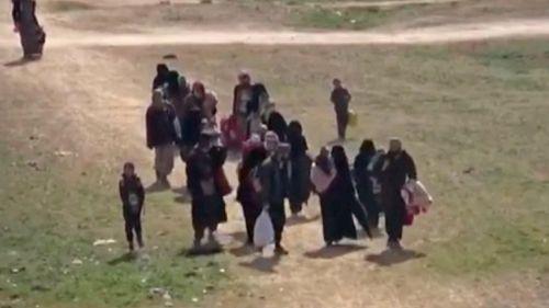 Civilians flee fighting near Baghouz, Syria.