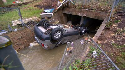 A Nissan Dualis has been found overturned in a drain at Bexley in Sydney's south after a wild storm hit the city overnight. (9NEWS)