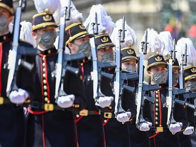Belgium's Crown Princess Elisabeth, fourth right, marches past the Royal tribune with cadets of the military school during the National Day parade in Brussels, Wednesday, July 21, 2021. Belgium celebrates its National Day on Wednesday in a scaled down version due to coronavirus, COVID-19 measures. (Laurie Dieffembacq, Pool Photo via AP)