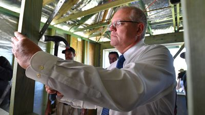 Scott Morrison hammers a nail at an investment property development in Port Macquarie.