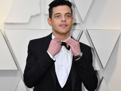 Rami Malek on the 2019 Oscars red carpet fixing his bow-tie