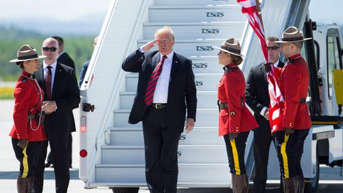 Mr Trump saluted Canadian Mounties as he was greeted at an airport at a military base in Quebec. Picture: CrowdSpark
