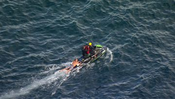 Five people have been rescued after a boat capsized off Sydney.
