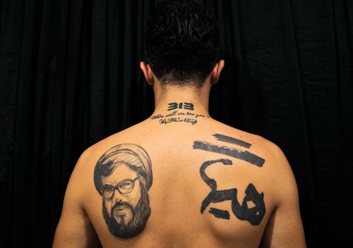 """A man poses for a photo showing off his tattoos of Hezbollah leader Hassan Nasrallah and Shiite Muslim religious slogans in the southern suburb of Beirut, Lebanon. The tattoo in Arabic reads, """"It is impossible to humiliate us."""" A growing number of Shiite Muslims in Lebanon are getting tattoos with religious and other Shiite symbols."""