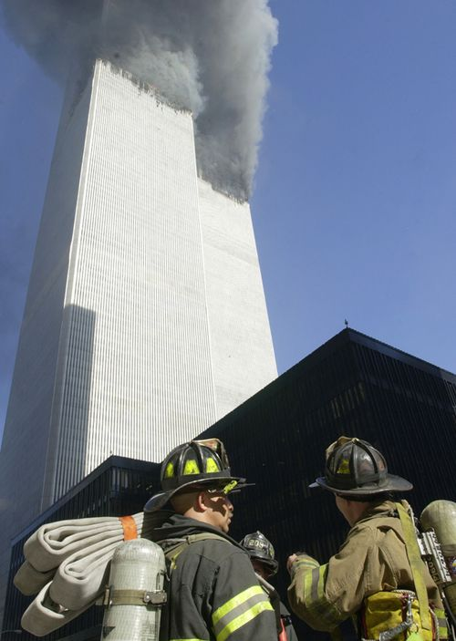Firefighters watch as smoke pours from the twin towers of the World Trade Center after planes hit them in a terrorist attack. (Getty)