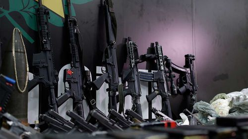 Weapons and drugs seized during a police raid are displayed for the press at city police headquarters in Rio de Janeiro, Brazil.