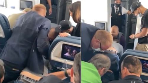 A man has been detained by passengers and crew after allegedly trying to storm the cockpit.