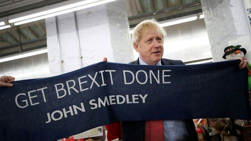 """UK Prime Minister Boris Johnson holds a scarf with slogan """"Get Brexit Done"""" as he visits John Smedley Mill on December 05, 2019 in Matlock, England"""