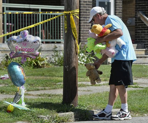 Paul Laughlin, 57, places stuffed animals outside the day care home in Pennsylvania, where five kids were killed in a fire.