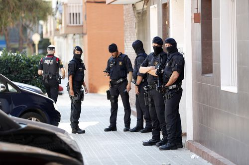 Several Mossos d'Esquadra officers stand guard outside the residential building where the man, who entered in a police station holding a knife and allegedly shouting 'Allah is great', lived in the town Cornella de Llobregat, in Barcelona, northeastern Spain