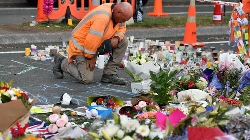 A worker grieves at a makeshift memorial at the Al Noor Mosque on Deans Rd in Christchurch.