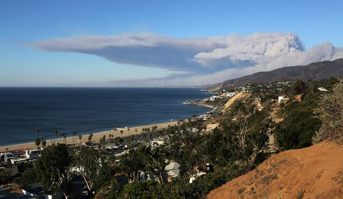 Strong winds blow smoke horizontally over the the Santa Monica Mountains and the Pacific Ocean over the city of Malibu.