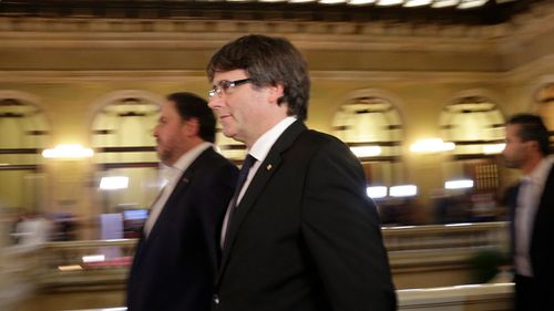 Catalan regional President Carles Puigdemont walks into the Catalan parliament. (Image: AP)