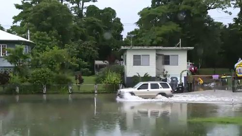 A driver in floodwaters in Mossman, north of Port Douglas. (9NEWS)