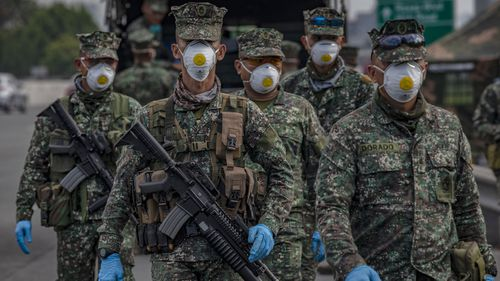 Filipino policemen wearing facemasks and gloves man a checkpoint as authorities begin implementing lockdown measures on March 16, 2020 in Las Pinas in Metro Manila.