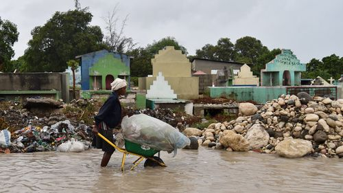 A woman pushes a wheelbarrow while walking in a partially flooded street, in the Haitian capital, Port-au-Prince. (AFP)