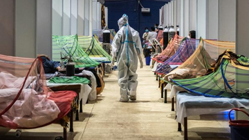 A medical worker observes patients inside a COVID-19 ward that was set up inside a sports stadium in New Delhi.