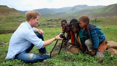 The young royal shows children a photograph he has taken on a Fuji X100s camera.