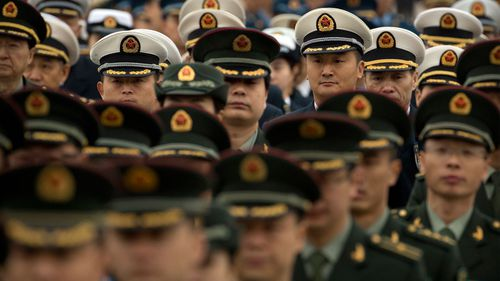 Military delegates arrive for a meeting at the Great Hall of the People ahead of Monday's opening session of China's National People's Congress (NPC)