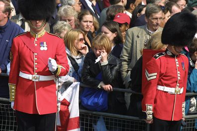 An onlooker weeps as the coffin carrying the Queen Mother departs from St. James Palace, followed by members of the Royal Family.