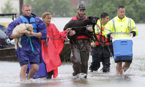Volunteers and Klein fire fighters carry pets and possessions of a rescued resident that was stranded in her home along the flooded Cypress Creek in Klein, a north suburb of Houston, Texas, on August 28, 2017. (AAP)