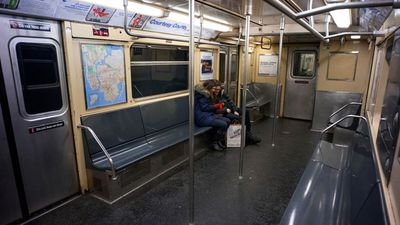 Two passengers ride on a subway car in New York. (AAP)