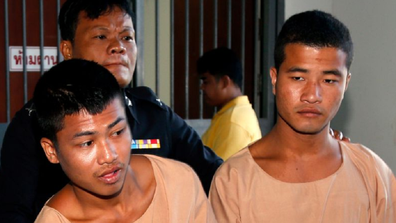 Zaw Lin (right) and Wai Phyo are escorted by a Thai police officer after they were sentenced to death.