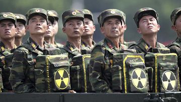 North Korean soldiers bear parcels marked with the nuclear symbol at a parade.