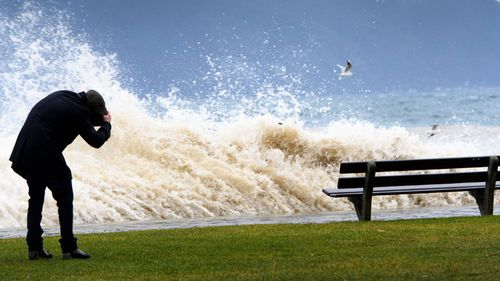 A man covers his head as waves pound the lakeside promenade on the Lake of Geneva. (AAP)