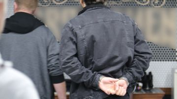 Police handcuff the accused inside a barber shop.