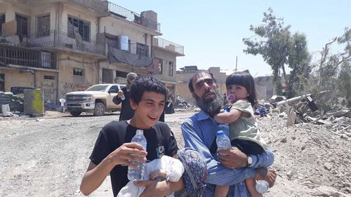 Locals in front of bullet-riddled homes in Mosul. (Owen Holdaway)