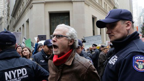 Police lead a man away in plastic cuffs after a protest of the tax overhaul plan in front of the New York Stock Exchange. (AP)