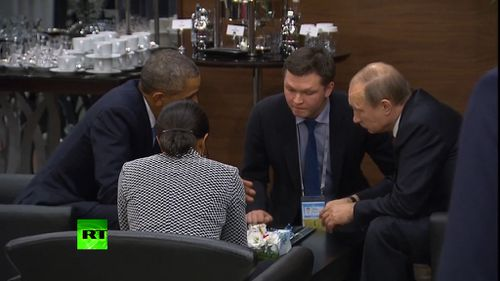 Mr Obama and Mr Putin speak with advisers after the Paris terror attacks.