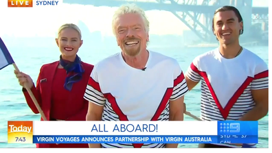 Sir Richard Branson pictured alongside a Virgin Australia and Virgin Voyages employee on Sydney Harbour.