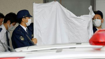 Police officers hide the face of arrested Japanese Yoshitane Yamasaki with a sheet while escorting him to a police vehicle to leave for Prosecutor's Office for further investigation, in Sanda City, western Japan. (AAP)