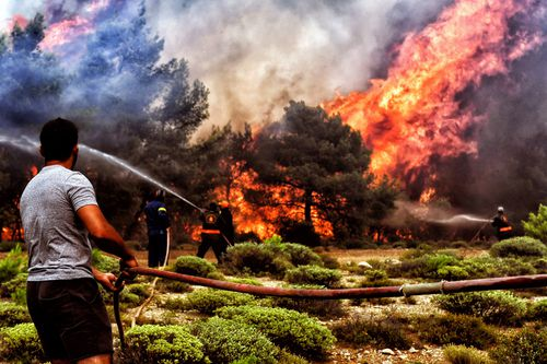 Firefighters and volunteers try to extinguish a wildfire raging in Verori. Picture: PA