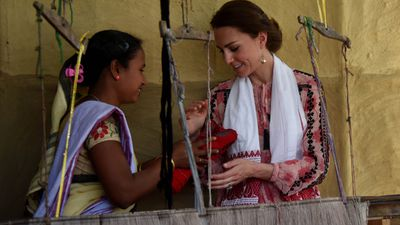 An Indian woman presents a handloom cloth to Kate in the Kaziranga village of Panbari, on day four of the tour.