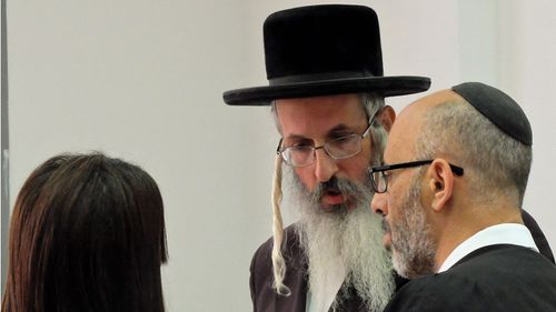 A supplied image obtained Sunday, May 8, 2016 of Malka Leifer's brother (C) speaks with Leifer's defence lawyer Yehuda Fried in the Jerusalem District Court.