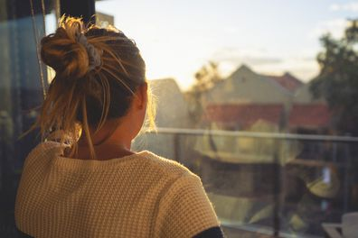 Woman looking out window, depressed.