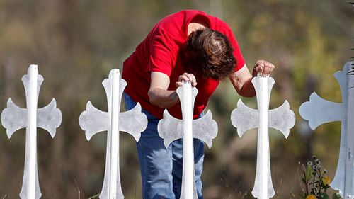 Maria Durand, a Bible study teachers aid at First Baptist Church of Sutherland Springs, leans over while hanging onto two of the 26 crosses representing the victims in Sutherland Springs, Texas. (AAP)