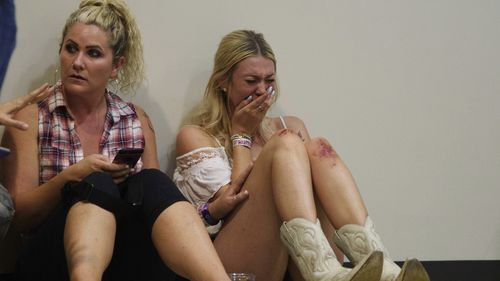 A woman cries while hiding inside the Sands Corporation plane hangar after the mass shooting. (AAP)