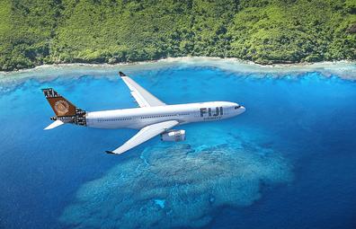 Fiji Airways plane flying over blue water along the Fiji coast