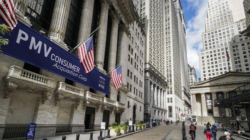 Pedestrians pass the New York Stock Exchange, Friday, Oct. 2, 2020, in New York