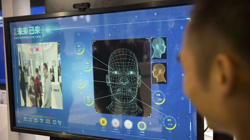 A man watches as a visitor tries out a facial recognition display at a booth for Chinese tech firm Ping'an Technology.