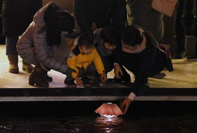People put a floating wish lamp onto water at Cheonggye street during New Year's Eve celebrations in Seoul, South Korea.