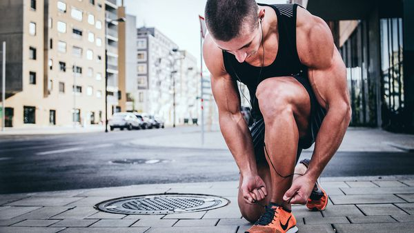 Fit man tying up shoes