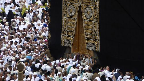In this Feb. 24, 2020, photo, Muslim pilgrims pray near the Kaaba, the cubic building at the Grand Mosque, as worshippers circumambulate around during the minor pilgrimage, known as Umrah in the Muslim holy city of Mecca