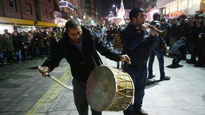 Two men surrounded by people play music as they gather to celebrate in Ankara. Jubilant residents began trickling back to Kobane after Kurdish fighters drove the Islamic State group from the town, which became a major symbol of resistance against the jihadists.