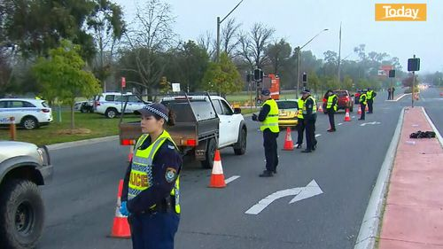 Police stop cars at the NSW-Victoria border.